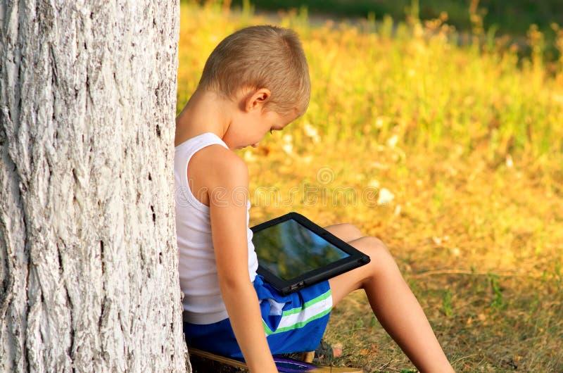 Jungen-Kind, das mit dem Tablet-PC im Freien spielt stockfotos