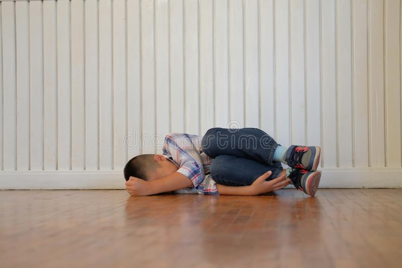 Jungen-Kinderkinder des deprimierten Umkippens traurige asiatische Kinder, dieauf Boden liegen lizenzfreie stockfotos