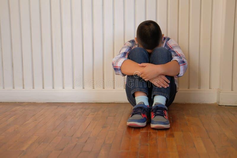 Jungen-Kinderkinder des deprimierten Umkippens traurige asiatische Kinder, dieauf floo sitzen stockfotos