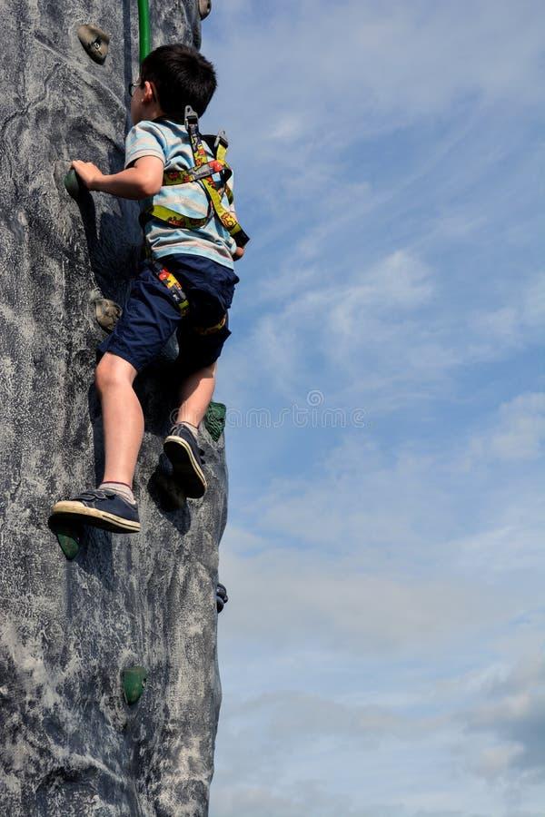 Jungen-Kletterwand draußen stockfotografie