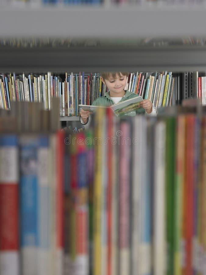 Jungen-Lesebuch in der Bibliothek lizenzfreies stockbild