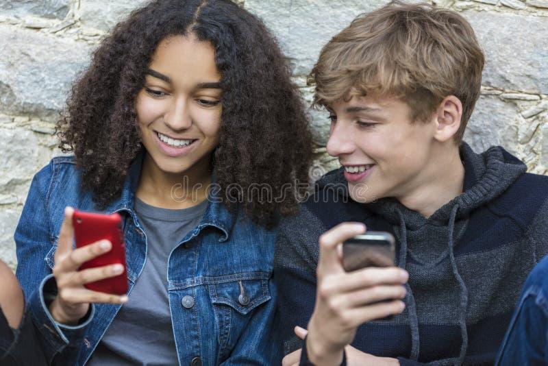 Jungen-Mädchen-männlich-weibliche Jugendliche, die Handy verwenden stockbild
