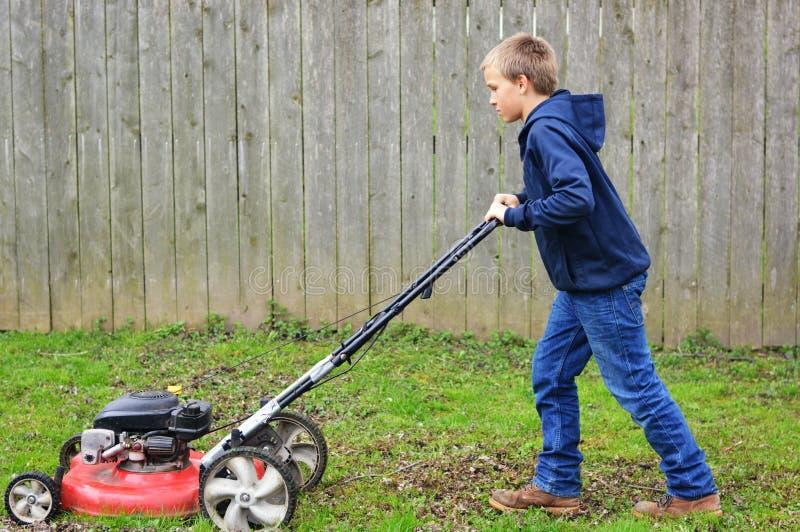 Jungen-mähender Rasen lizenzfreie stockfotos