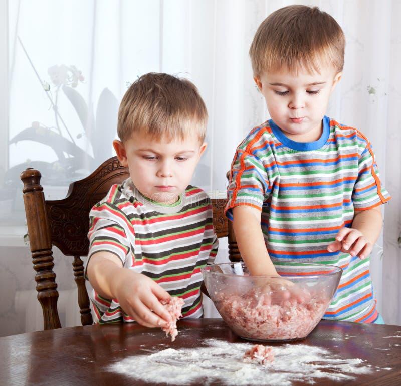 Jungen mischen Hackfleisch in einer Schüssel stockbilder