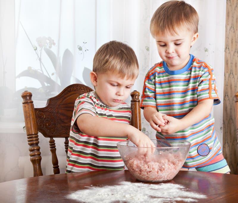 Jungen mischen Hackfleisch in einer Schüssel lizenzfreies stockfoto