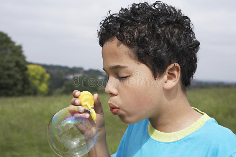 Jungen-Schlagseifenblase auf dem Gebiet stockbilder
