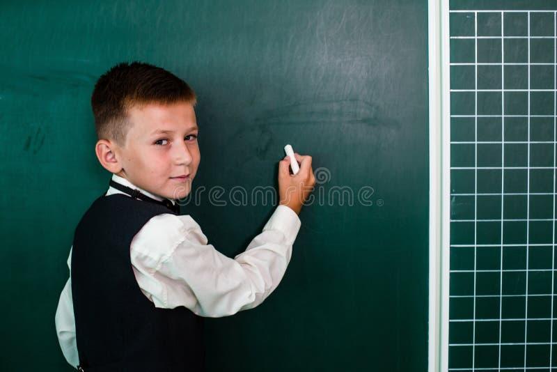 Jungen-Schreiben auf der Tafel lizenzfreie stockbilder