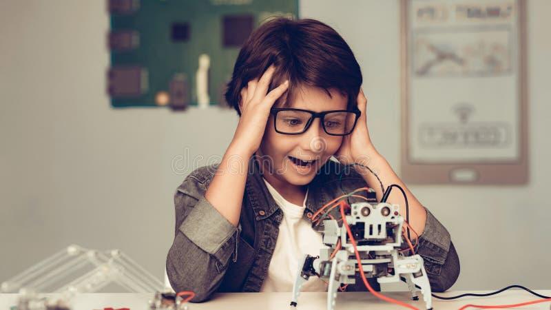 Jungen-Sitzen am Schreibtisch und zu Hause am konstruieren Roboter lizenzfreie stockfotos