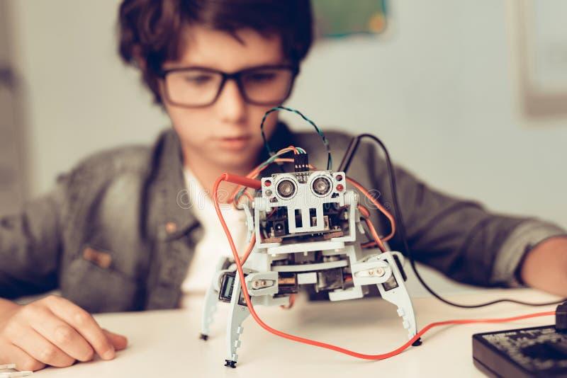 Jungen-Sitzen am Schreibtisch und zu Hause am konstruieren Roboter stockfotos
