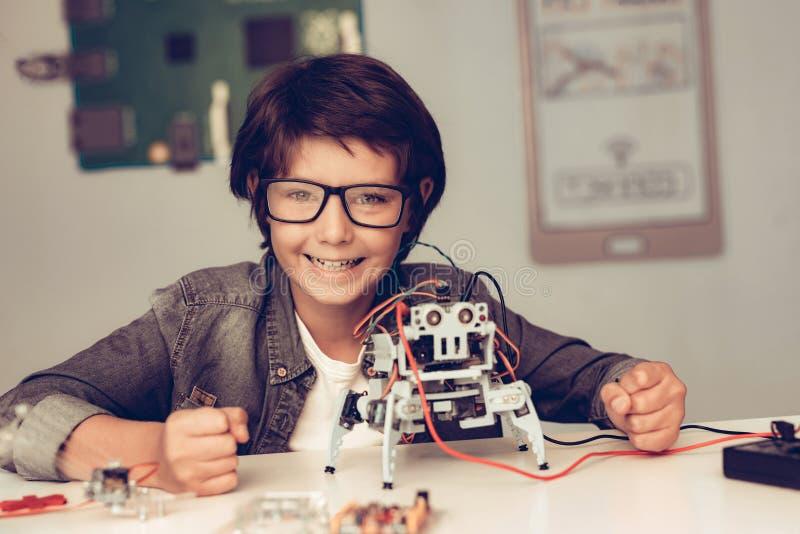 Jungen-Sitzen am Schreibtisch und zu Hause am konstruieren Roboter stockbild