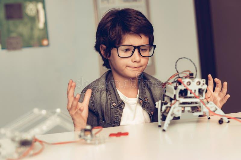 Jungen-Sitzen am Schreibtisch und zu Hause am konstruieren Roboter stockbilder