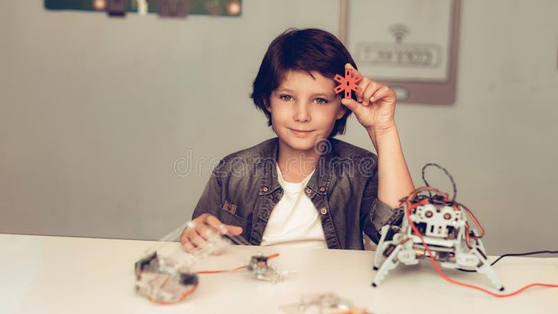 Jungen-Sitzen am Schreibtisch und zu Hause am konstruieren Roboter lizenzfreies stockbild