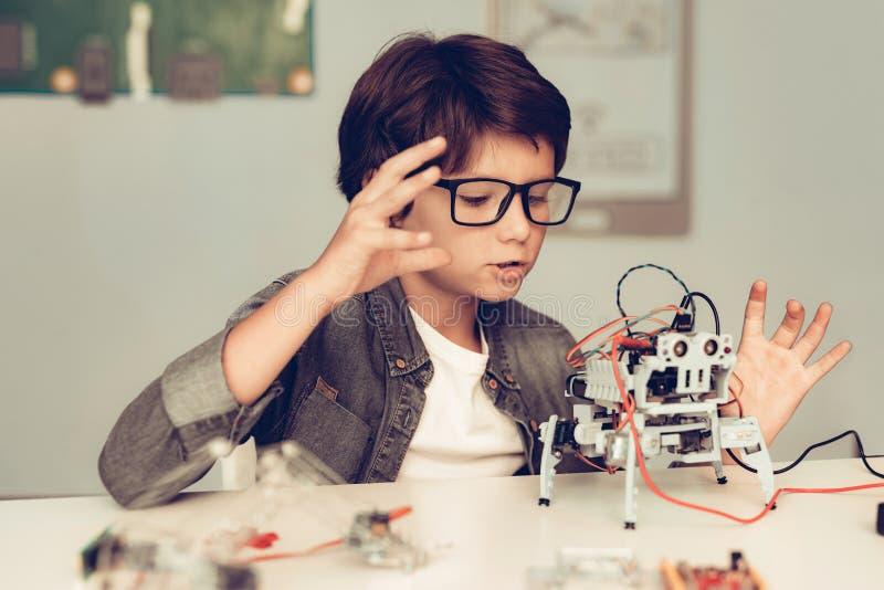 Jungen-Sitzen am Schreibtisch und zu Hause am konstruieren Roboter lizenzfreie stockfotografie