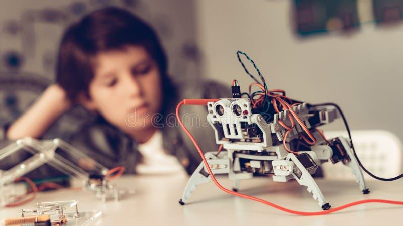 Jungen-Sitzen am Schreibtisch und zu Hause am konstruieren Roboter lizenzfreies stockfoto