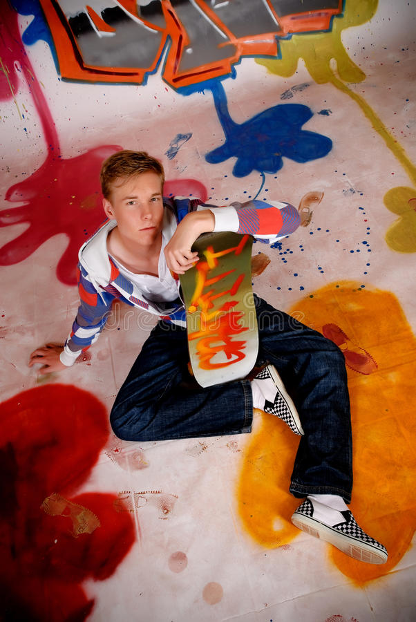 Jungen-Skateboard, Graffitiwand stockfotos