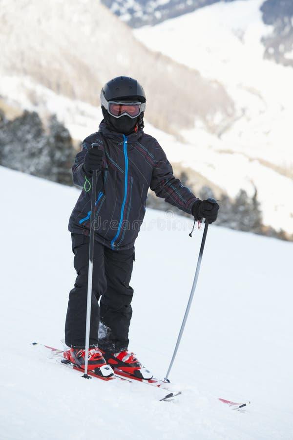 Jungen-Skifahrer steht auf schneebedeckter Steigung stockfotografie