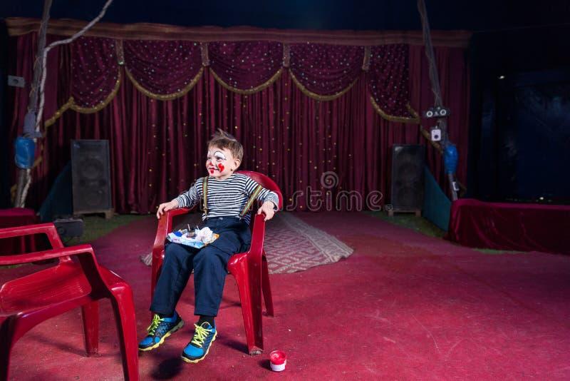 Jungen-tragender Clown Makeup Sitting im Stuhl auf Stadium lizenzfreie stockfotografie