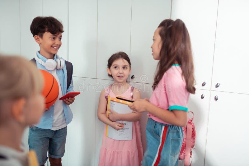 Jungen und Mädchen, die beim Bruch in der Schule genießen nett sich fühlen stockfotografie
