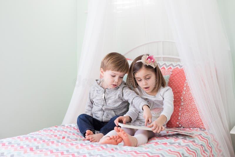 Jungen-und Mädchen-Lesung im Bett stockbild