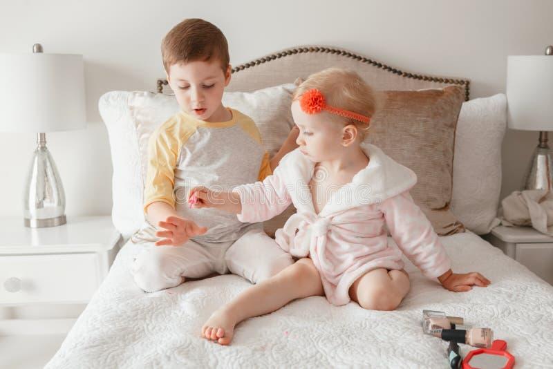 Jungen- und Mädchengeschwister, welche die zusammen malenden Nägel zu Hause sitzen auf Bett spielen lizenzfreie stockfotos