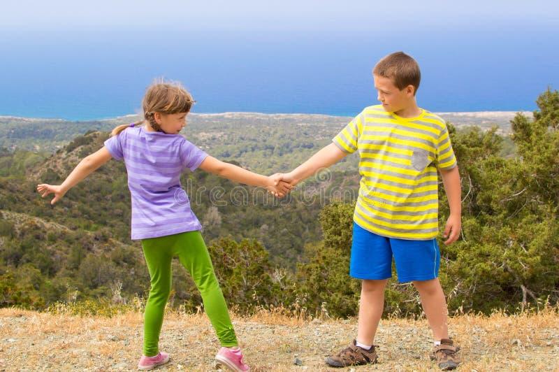 Jungen- und Mädchenholdinghände stockbilder