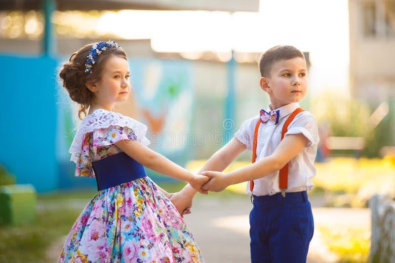 Jungen- und Mädchenholdinghände Valentine& x27; s-Tag Mädchen und Junge küssen im Garten stockfoto