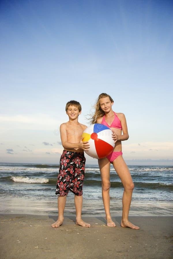 Jungen- und Mädchenholdingkugel lizenzfreie stockbilder