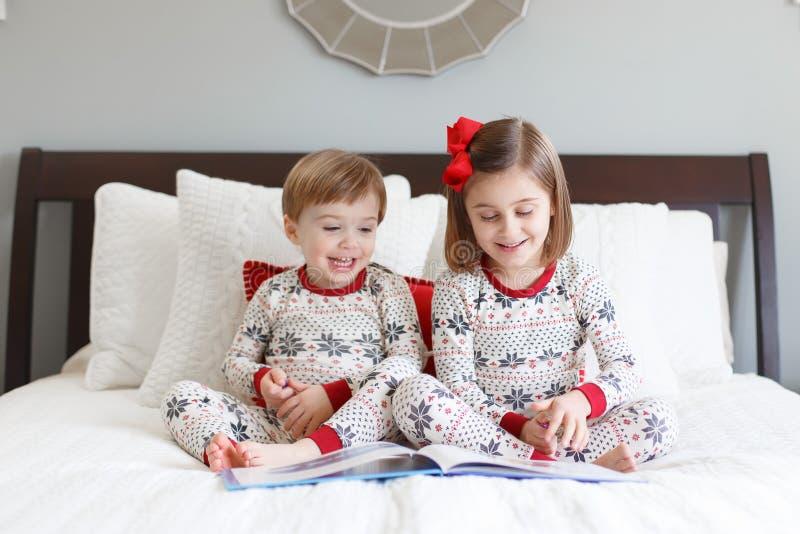 Jungen- und Mädchenlesung auf Bett mit Weihnachtspyjamas lizenzfreie stockfotografie