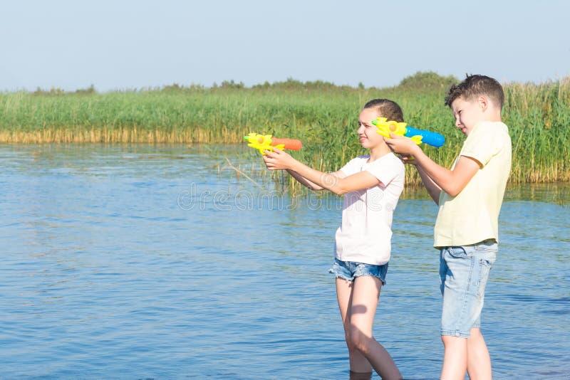 Jungen- und Mädchenspiel mit Wasserpistolen auf dem Fluss lizenzfreies stockfoto