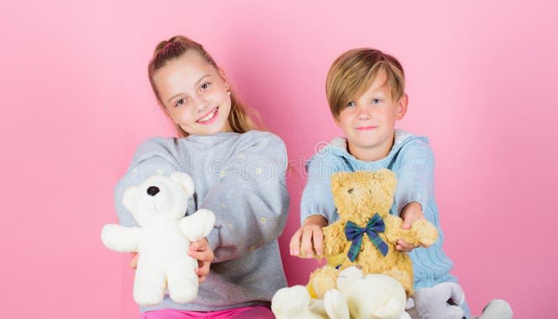 Jungen- und Mädchenspiel mit weichem Spielwarenteddybären betreffen rosa Hintergrund Bärnspielwarensammlung Teddybären helfen Kin lizenzfreies stockfoto