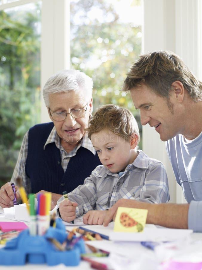 Jungen-Zeichnung mit Zeichenstiften mit Vater And Grandfather lizenzfreie stockfotos