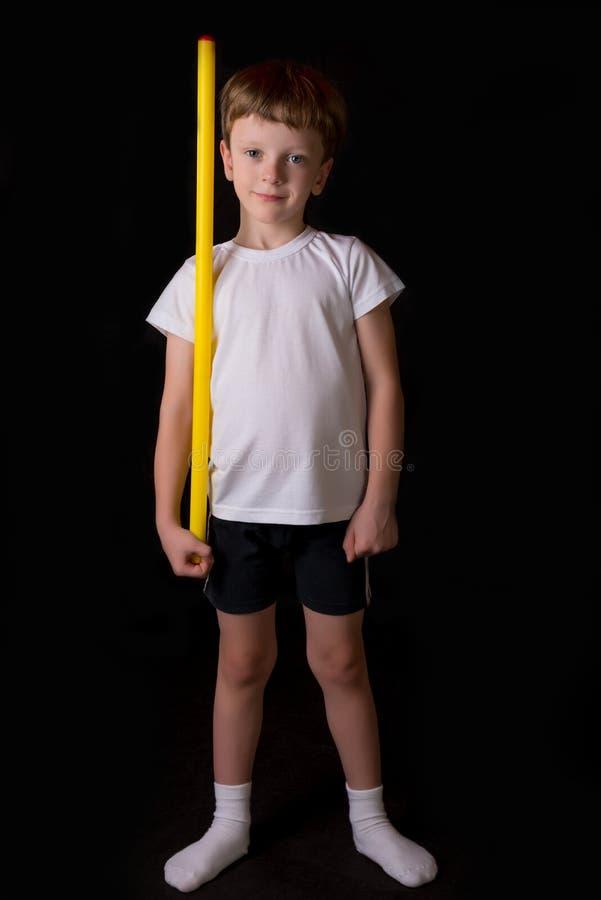 Jungenathlet führt Übungen mit gymnastischem Stock in der Turnhalle durch lizenzfreie stockfotografie