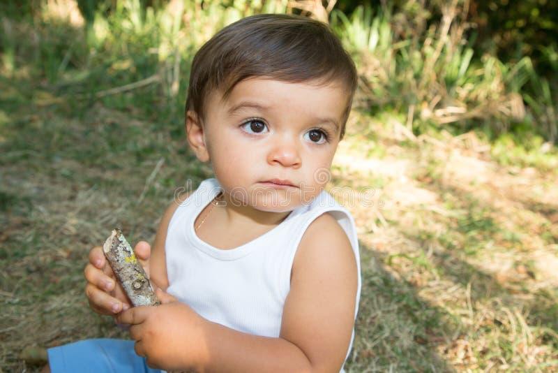 Jungenblickseite des Porträts kleines Kindersitzen auf Grasgarten lizenzfreies stockbild