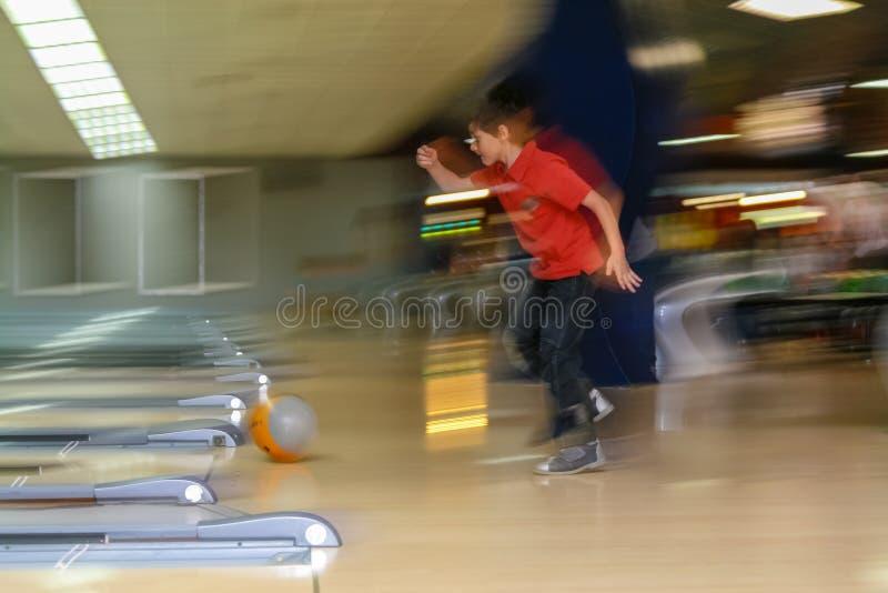 Jungenbowlingspiel am Verein, der seinen Erstschlag hat lizenzfreie stockbilder