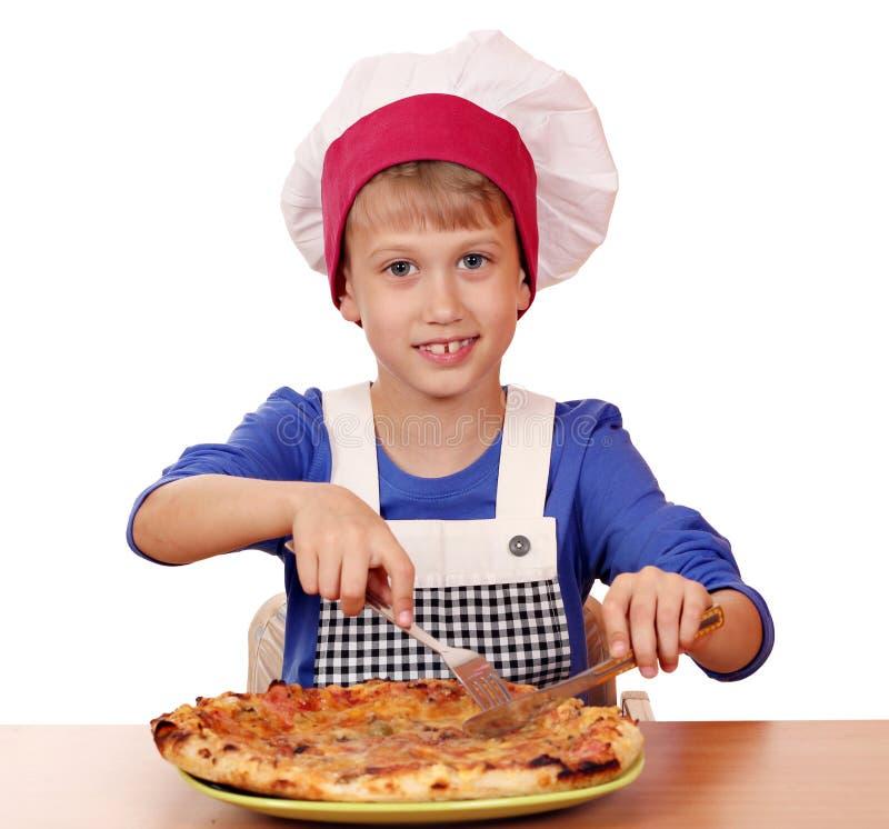 Jungenchef, der Pizza isst lizenzfreies stockbild