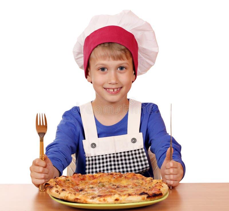 Jungenchef essen Pizza lizenzfreies stockbild