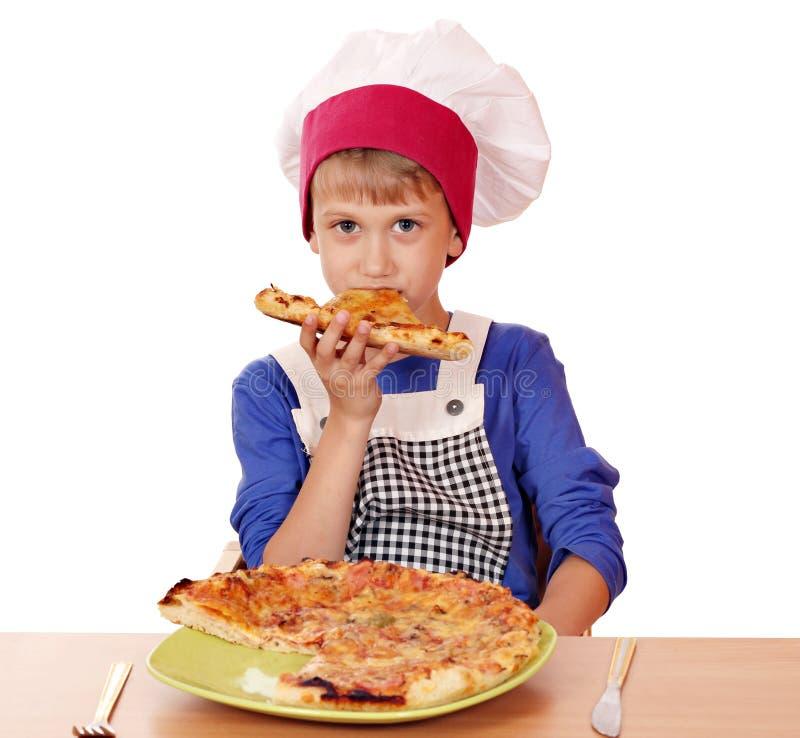 Jungenchef essen Pizza stockfotografie
