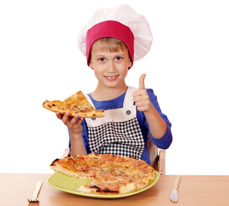 Jungenchef mit Pizza und dem Daumen oben stockfotos