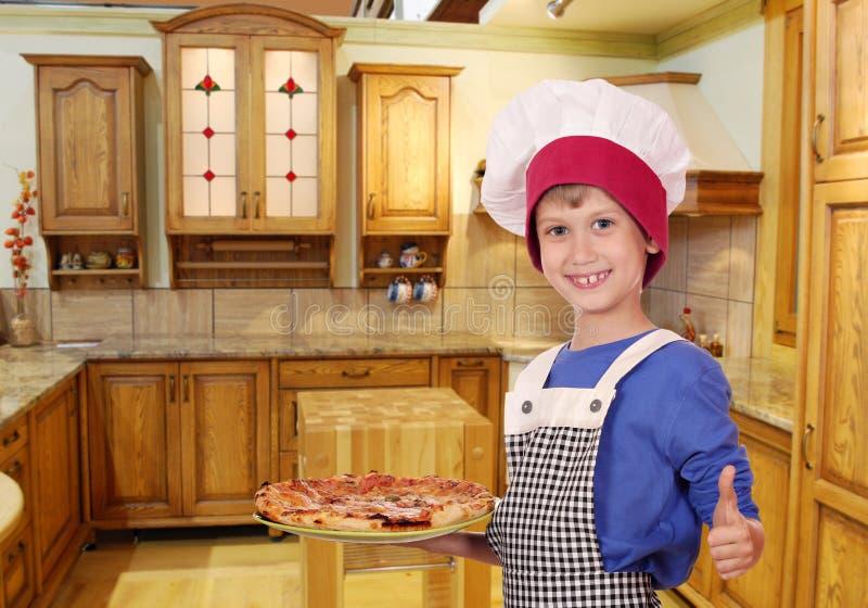 Jungenchef mit Pizza und dem Daumen oben stockbilder