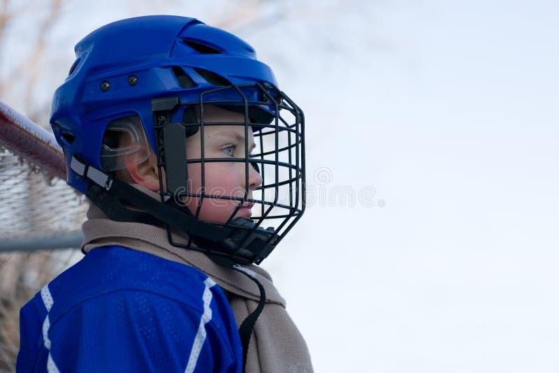 Jungeneis-Hockeyspieler spielt Hockey lizenzfreie stockfotos