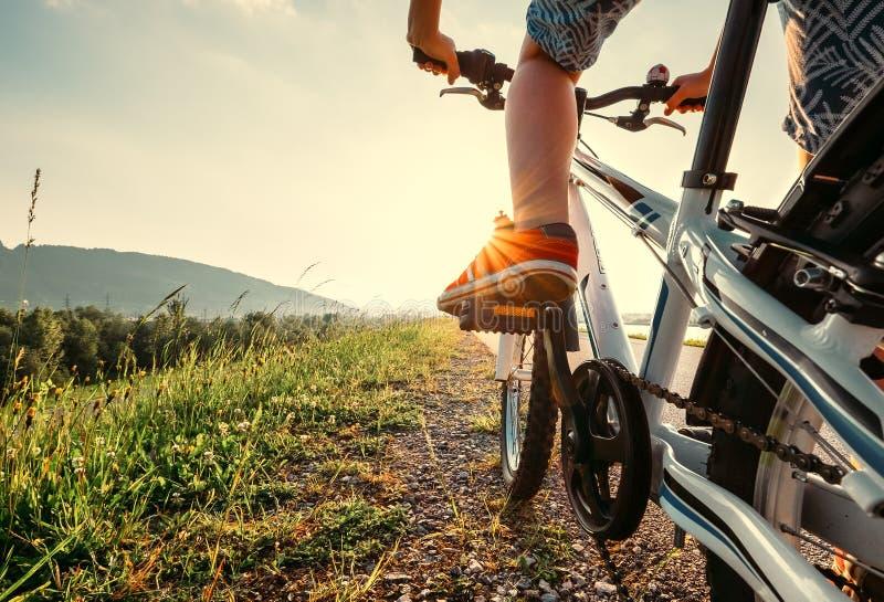 Jungenfüße in den roten sneackers auf Fahrradpedalabschluß herauf Bild lizenzfreie stockbilder