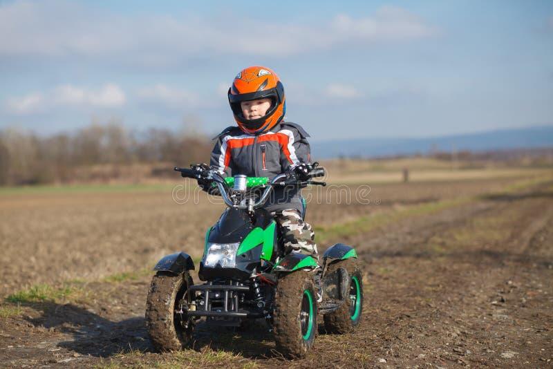 Jungenfahrten auf elektrisches ATV-Viererkabel stockfotografie