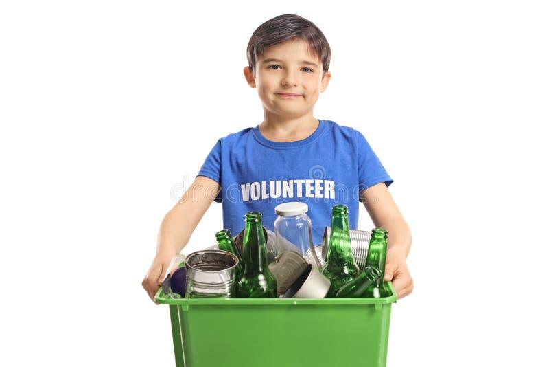 Jungenfreiwilliger, der einen Kasten mit der Wiederverwertung von Flaschen und von Dosen hält stockbilder