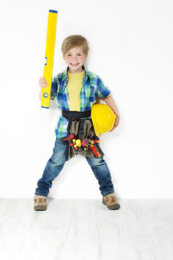 Jungenheimwerker mit Gurt des harten Hutes, der Stufe und des Hilfsmittels lizenzfreie stockfotos
