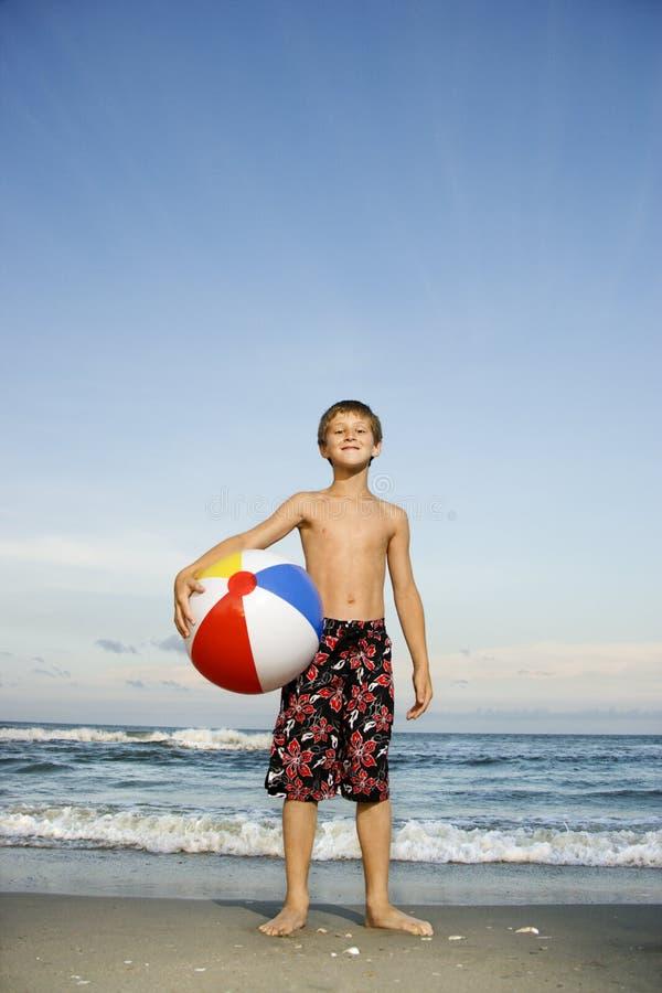 Jungenholding beachball auf Strand. lizenzfreie stockfotografie