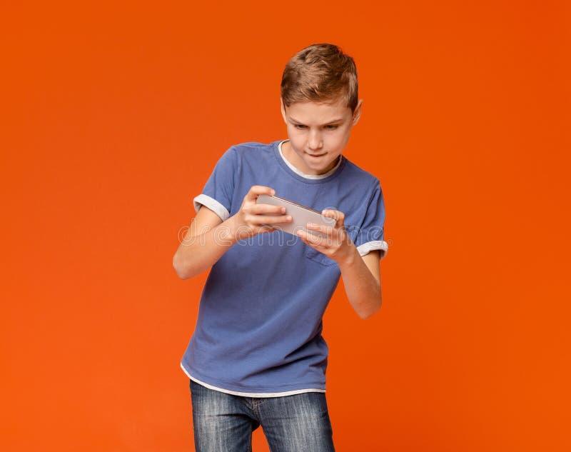 Jungenholdingmobiltelefon und spielen Videospiele lizenzfreie stockfotos