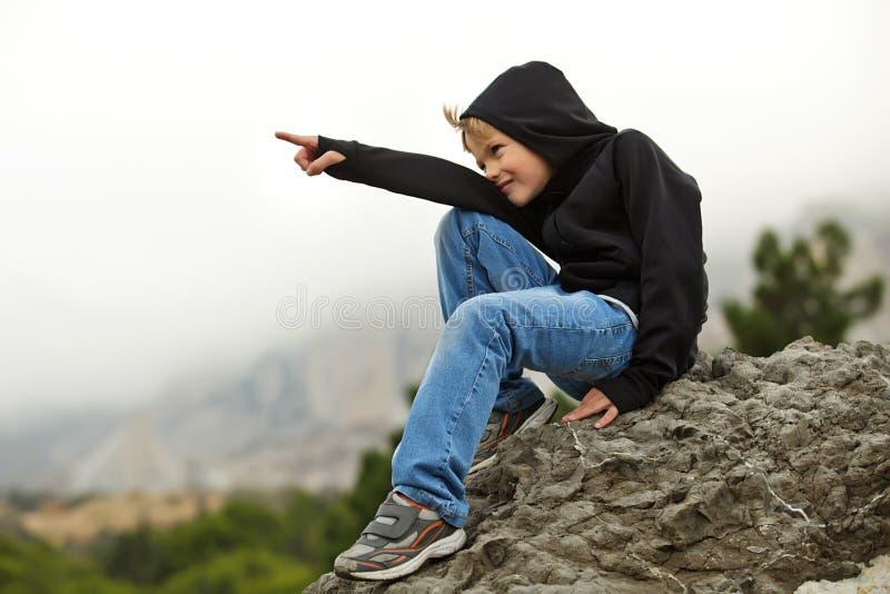 Jungenjugendlicher in der Sportkleidung, die auf dem Felsen sitzt lizenzfreies stockfoto