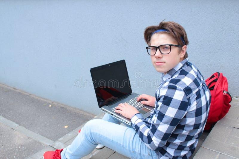 Jungenjugendlichschüler oder -student sitzt auf der Treppe und arbeitet im Computer, tragende Gläser, in einem Hemd und lächelt,  lizenzfreies stockfoto