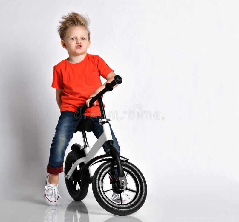 Jungenjunge im orange T-Shirt und in den Blue Jeans stellt vor sich, dass er schnell sein neues kühles Fahrrad ohne Pedale fährt  stockbilder