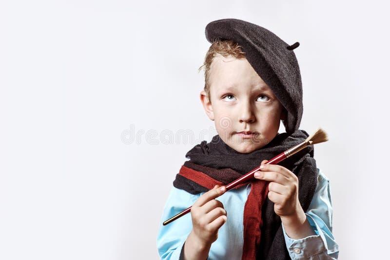 Jungenkünstler im schwarzen Barett und im Pinsel in der Hand auf einem hellen Hintergrund stockbilder